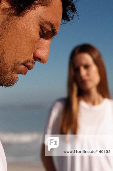 Profil eines Mannes mit einer Frau im Hintergrund