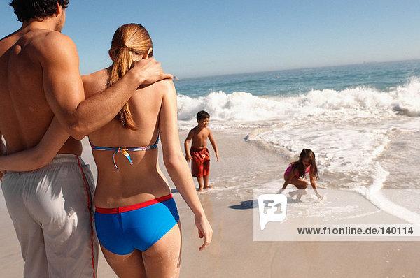 Eltern schauen Kindern beim Spielen am Strand zu.