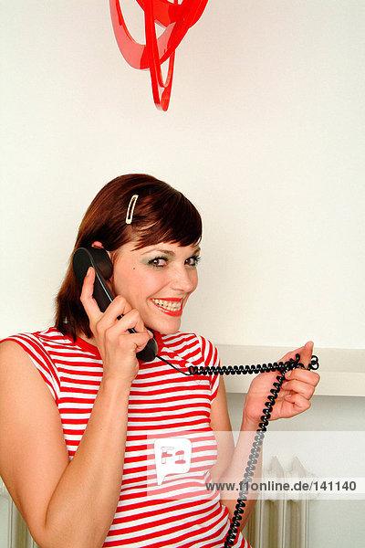 Lächelnde junge Frau am Telefon