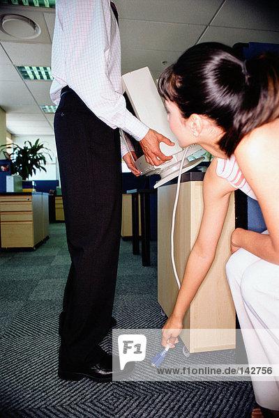 Zwei Büroangestellte beim Anheben eines Computers
