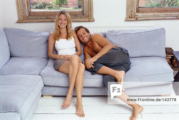 Paar sitzt zusammen auf dem Sofa