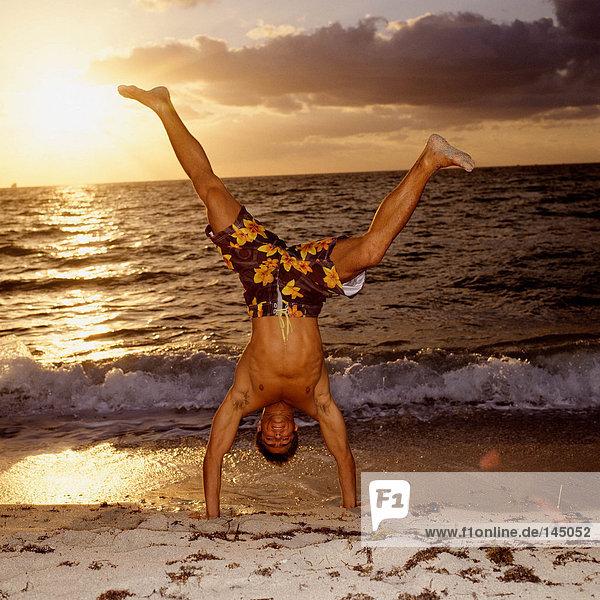 Mann beim Handstand am Strand