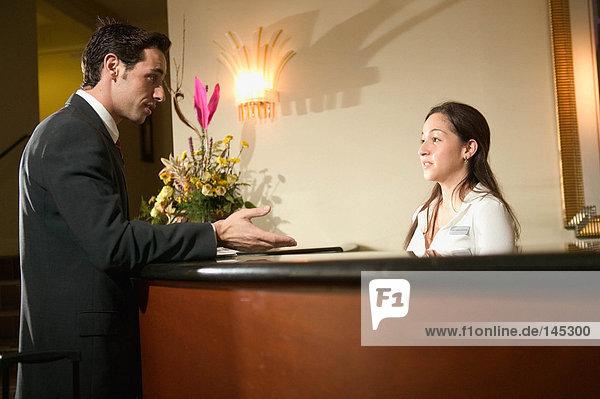 Ein Geschäftsmann und Rezeptionist im Gespräch