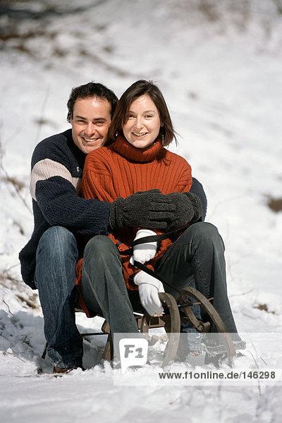 Paar auf dem Schlitten sitzend Paar auf dem Schlitten sitzend