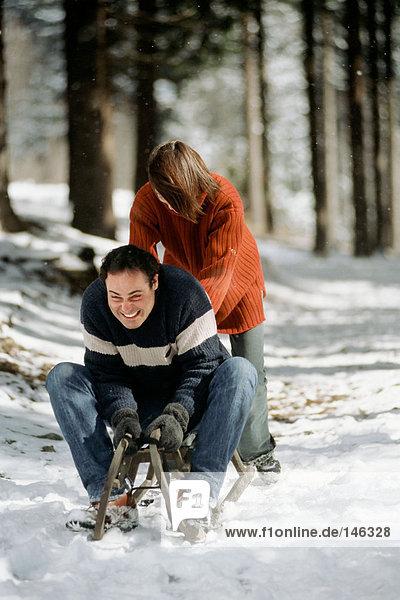 Paar spielt auf dem Schlitten Paar spielt auf dem Schlitten