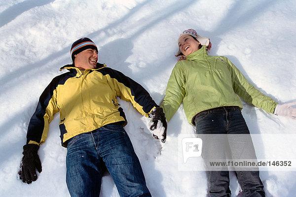 Paar im Schnee liegend