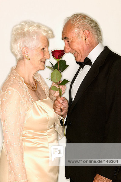 Seniorenpaar schnüffelt Rose