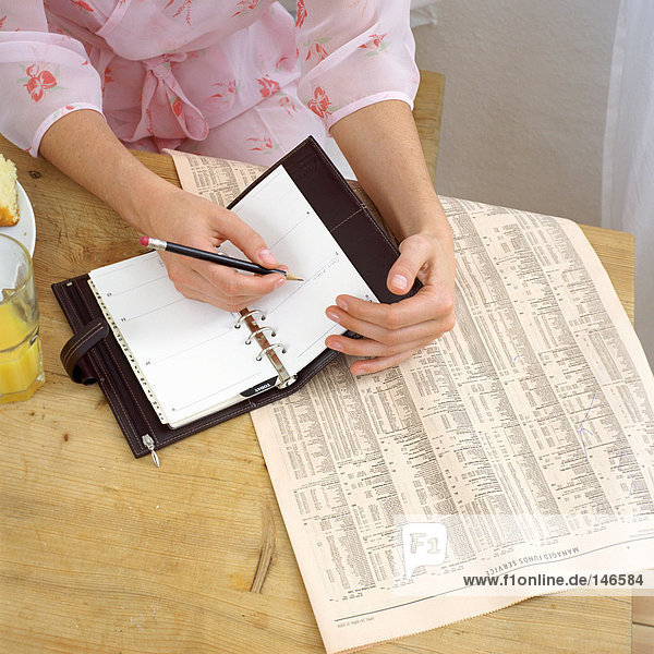 Woman with diary at breakfast