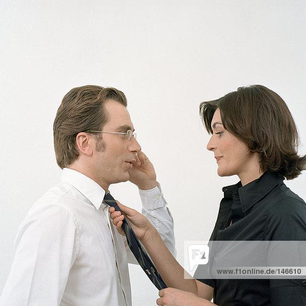 Frau stellt Krawatte auf Mann ein