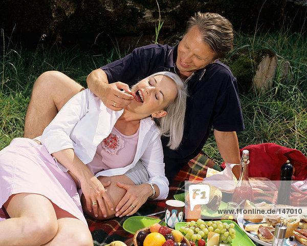Couple enjoying picnic meal.