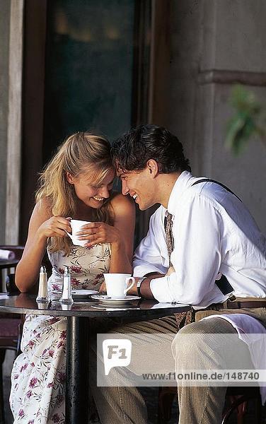 Junges paar lächelnd in Straßencafé