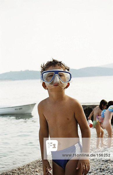 Junge steht am Kiesstrand