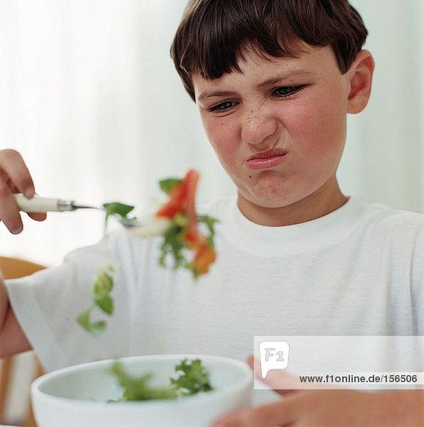 Junge schaut angewidert auf Salat