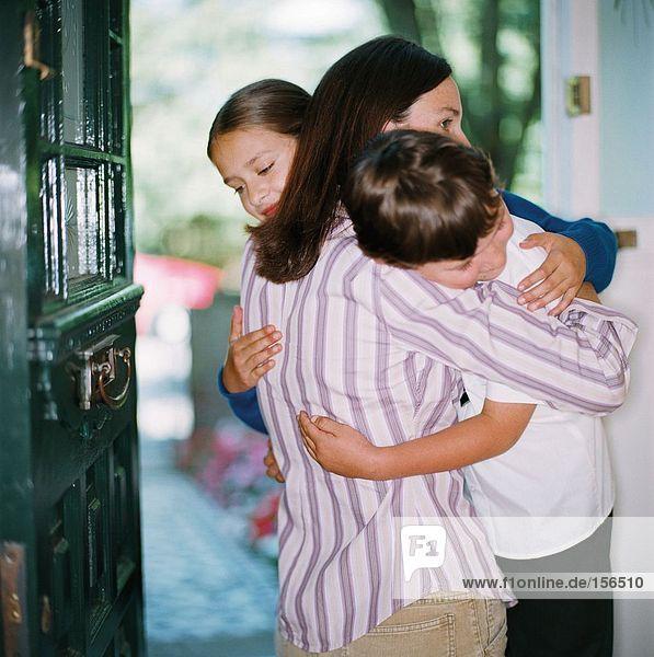 Mutter umarmt ihre Kinder in der Tür.