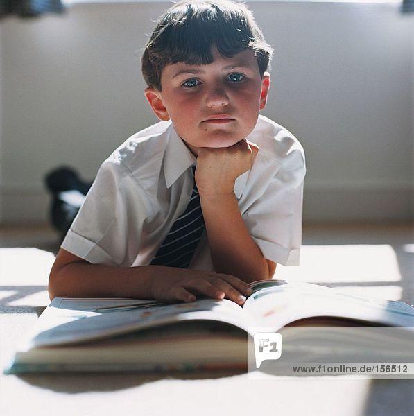 Junge macht Hausaufgaben auf dem Boden