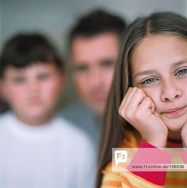 Seriöses Mädchen mit Vater und Bruder