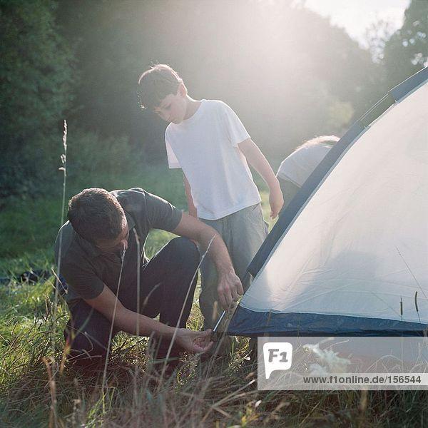 Vater und Sohn bauen ein Zelt auf