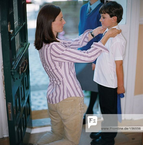 Frau zieht ihren Sohn für die Schule an