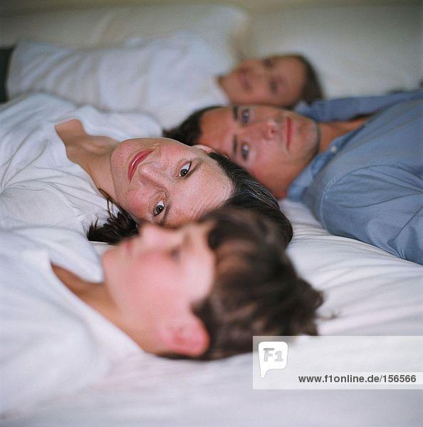 Familie entspannt auf dem Bett