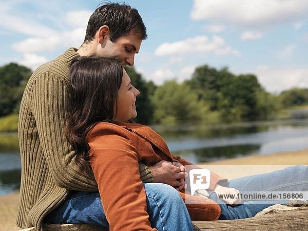 Junges Paar am See sitzend
