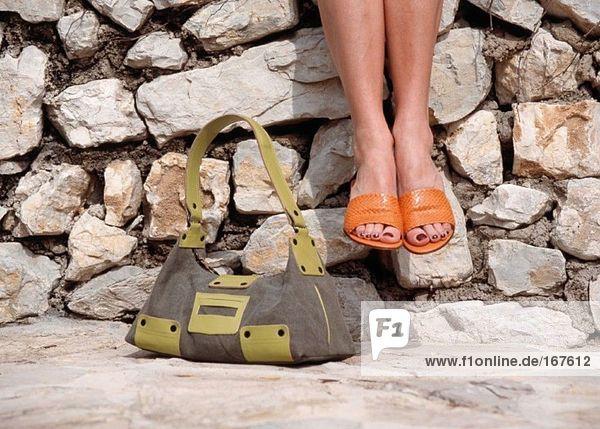 Frau auf der Wand sitzend mit Handtasche  niedrige Sektion