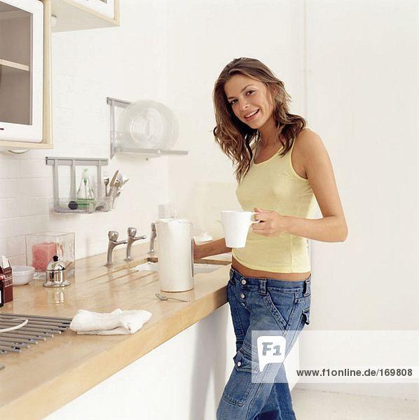 Junge Frau macht heißes Getränk