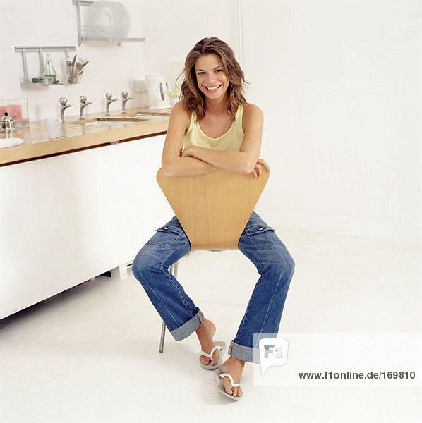 Junge Frau auf einem Stuhl in der Küche
