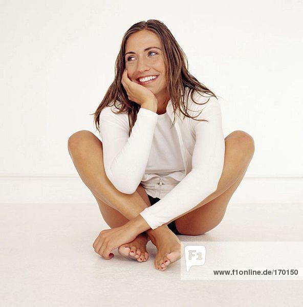 Junge Frau sitzend mit gekreuzten Beinen