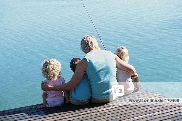 Vater mit Kindern am Steg