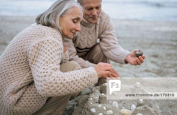 Seniorenpaar beim Bau einer Sandburg