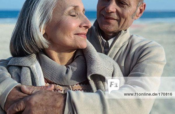 Seniorenpaar beim Umarmen am Strand