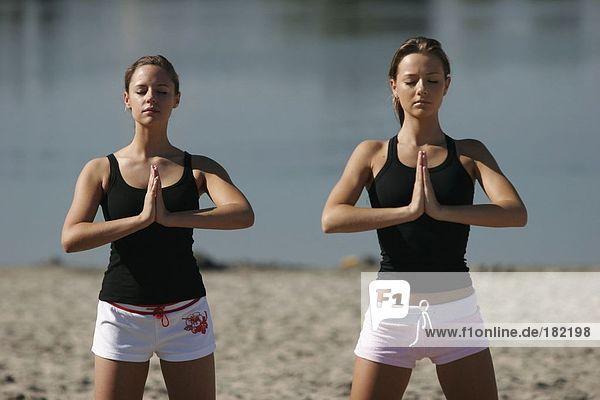 Two young women doing yoga on lake beach