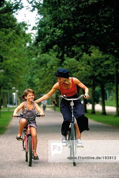 Frauen und Mädchen Radfahren auf Straße