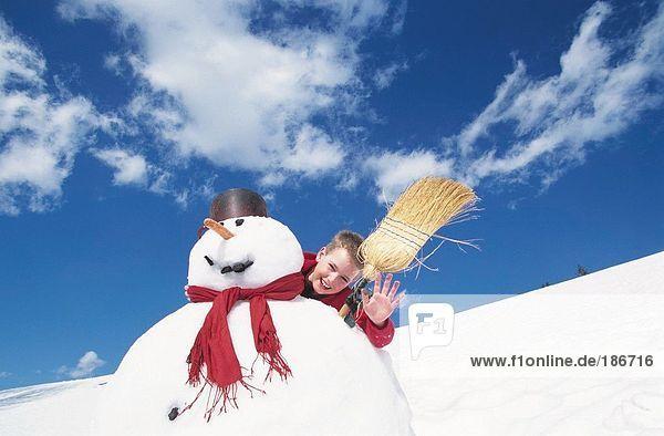 Boy behind snowman with broom