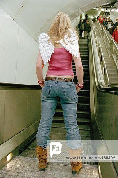 Frau steht in der Nähe der Rolltreppe