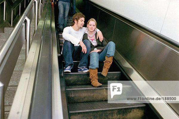 Paar auf Rolltreppe sitzend