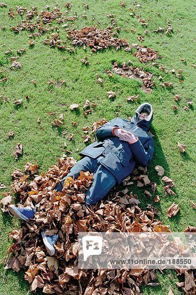 Mann schläft auf Blättern