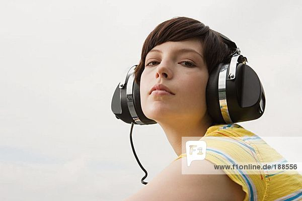 Junge Frau hört Musik auf dem Dach