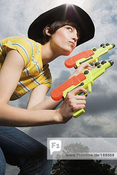 Frau spielt mit Spielzeugpistolen