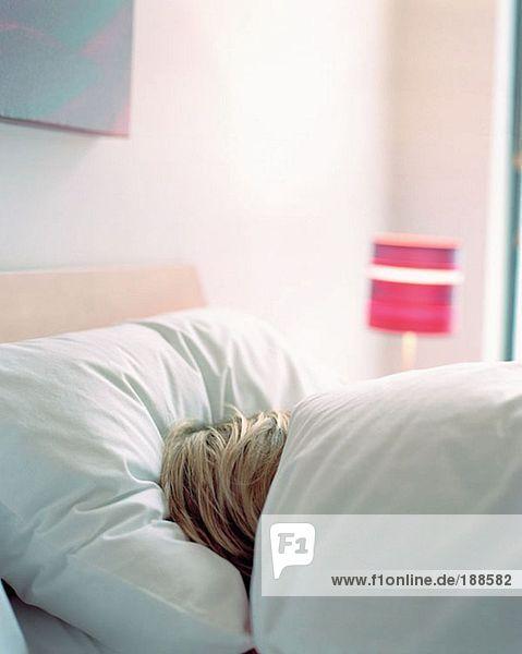 Frau schläft in einem Bett