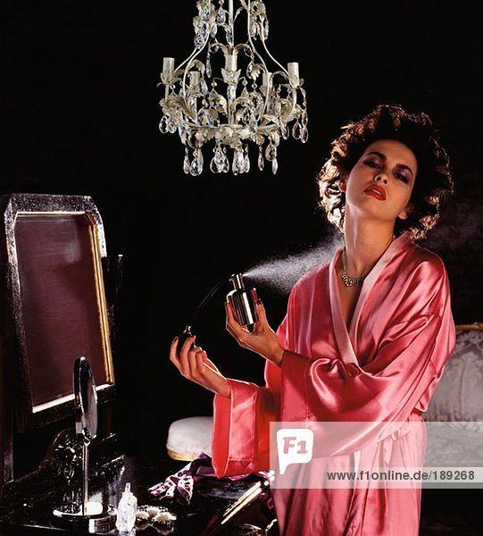 Junge Frau spritzt Parfüm
