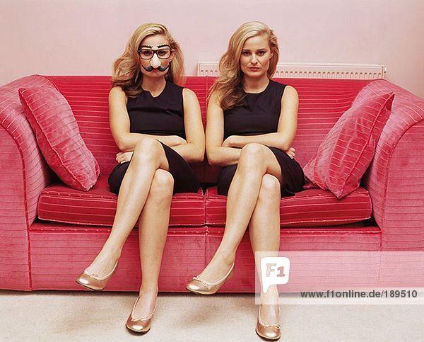 Zwei Frauen auf einem Sofa  eine in einer Komödie verkleidet.