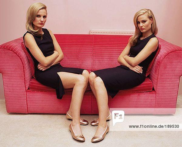 Zwei Frauen mit gekreuzten Armen auf dem Sofa