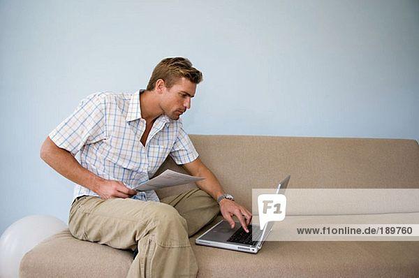 Mann begleicht Rechnung online