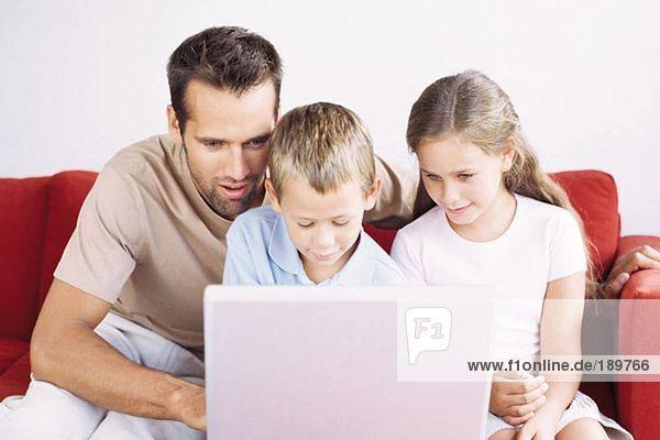 Vater und Kinder mit Laptop