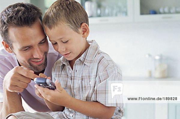 Vater zeigt dem Sohn  wie man das Handy benutzt.