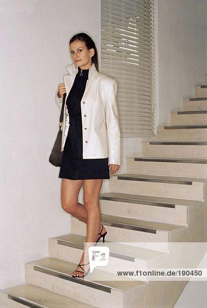 Frau  die die Treppe hinuntergeht.