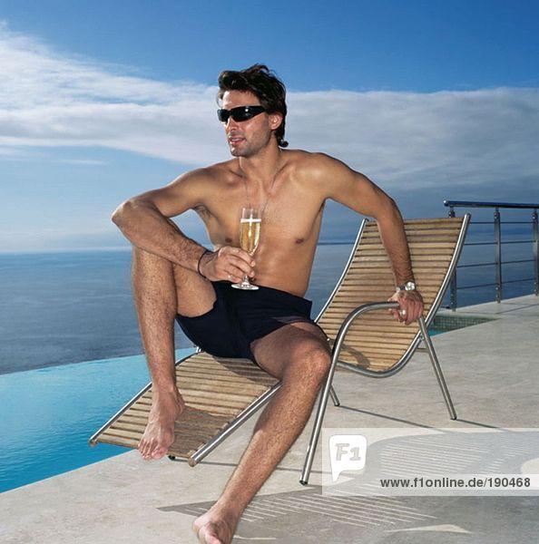 Mann auf einer Sonnenliege mit Champagnerglas