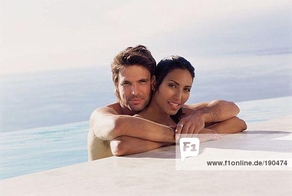 Paar am Rande des Swimmingpools