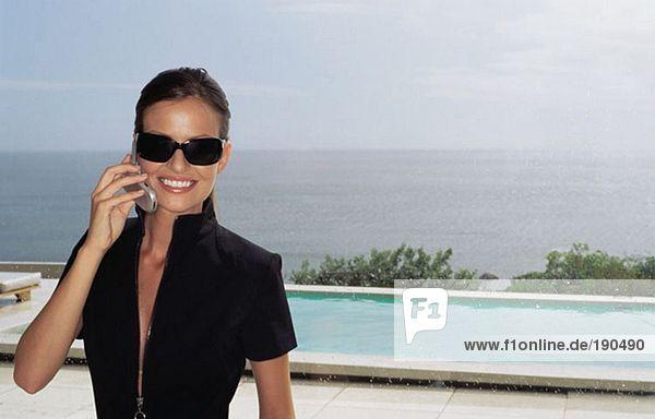 Frau mit Handy am Schwimmbad
